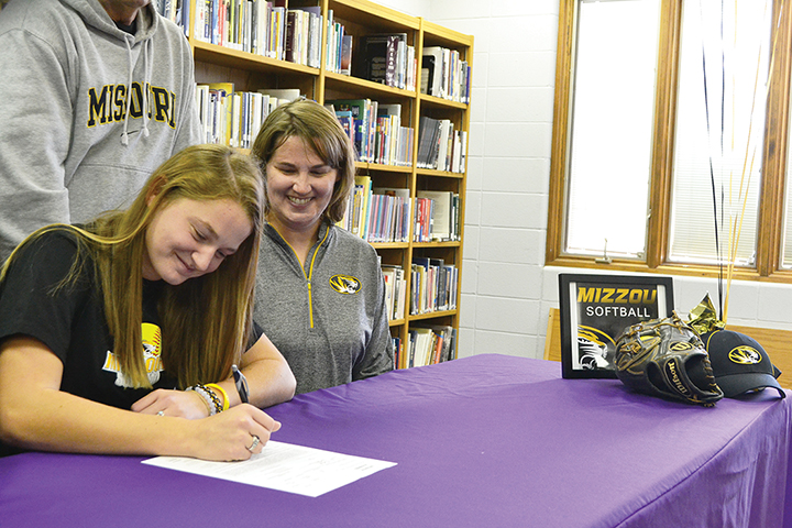 BRYCE MERENESS/Citizen photo Regan Nash, left, signs her national letter of intent to play softball at the University of Missouri during a ceremony Nov. 12 in the North Platte High School library in Dearborn, Mo., as her mother Kim looks on.