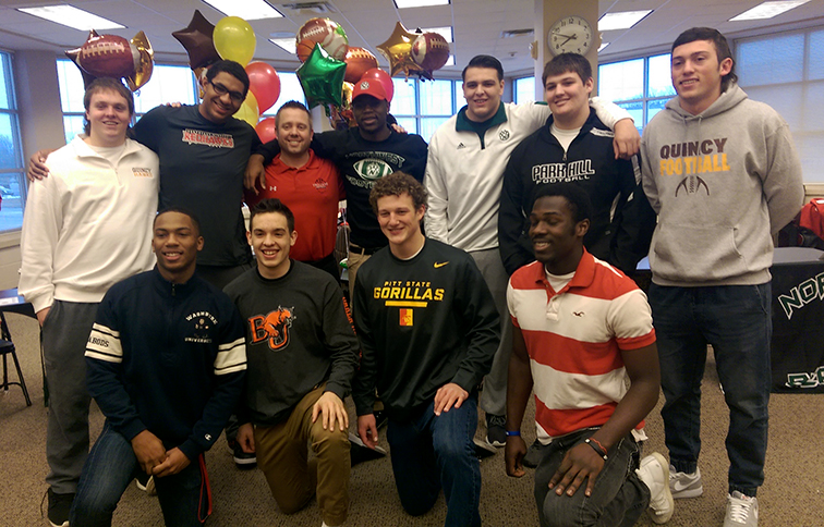 BRYCE MERENESS/Citizen photo Members of the Park Hill football's signing class pose with Park Hill coach Josh Hood.  First row, from left: Kenyatte Harris, David Taylor, Carter Anchors and Jeremiah Benson. Back row, from left: Austin Reiter, Ryan Truvillion, Hood, Jamaal Brazil, Anthony Enriquez, Jordan Lashbrook and Clayton Cole.