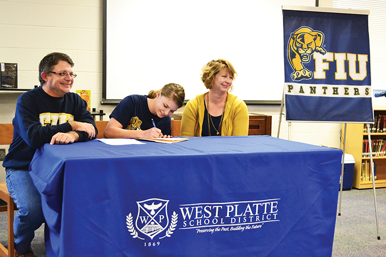 BRYCE MERENESS/Citizen photo West Platte senior Abby Summers, center, pens her national letter of intent to play softball at Florida International University in a ceremony Nov. 19 at West Platte High School.