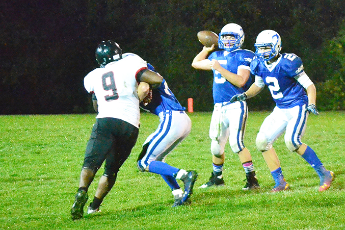 BRYCE MERENESS/Citizen photo West Platte quarterback Cody Guthrie, center, attempts a pass during a Oct. 10 game at Rudolph Eskridge stadium in Weston, Mo., while Plattsburg's Le'Aaron Hicks (9) rushes him.