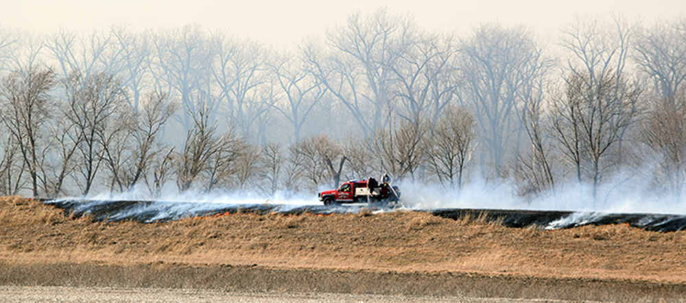 BRYCE MERENESS/Citizen photo   Members of the Camden Point Fire Protection District spray water on a blackened levee during a large grass fire Thursday, Feb. 18 near Beverly, Mo. The fire consumed about 1,500 acres of land.