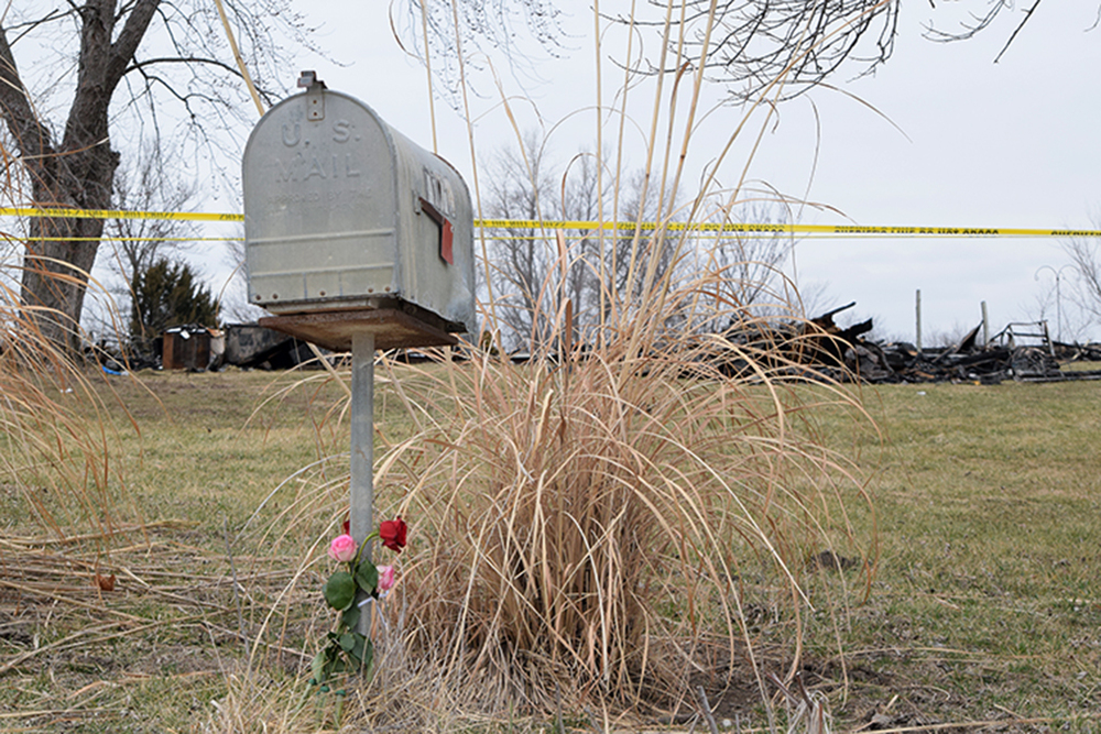 BRYCE MERENESS/Citizen photo   Four flowers adorn the mailbox at 4170 Buena Vista Rd. in Edgerton, Mo. with caution tape denoting the edge of the crime scene in a quadruple homicide investigation. The house was reduced to rubble in a fire on Friday, Feb. 19, and four bodies were discovered outside, also burned.