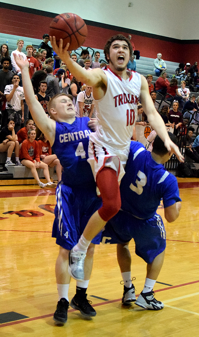 BRYCE MERENESS/Citizen photo Park Hill senior Brandon Townsell, center, draws contact while going up for a layup in between two St. Joseph Central defenders Friday, Feb. 19 at Park Hill High School in Kansas City, Mo. Park Hill won 65-44 to sweep the Suburban Conference Red Division season series with the Indians.