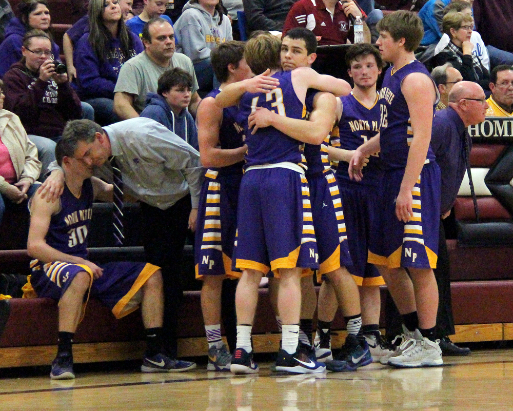 ROSS MARTIN/Citizen photo North Platte coach Tim Sutton, left, hugs senior Kyle Ewing while the rest of the Panthers players share a moment during the closing seconds of a Class 2 District 16 loss to Hamilton on Thursday, Feb. 25 at Maysville High School in Maysville, Mo.