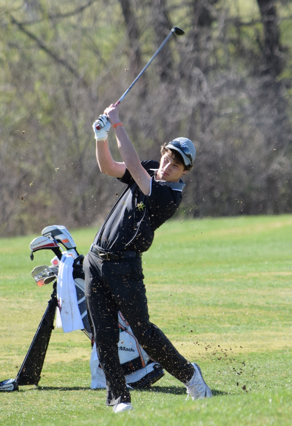 BRYCE MERENESS/Citizen photo Grass flies as Platte County senior Matt Madill hits an approach shot on Monday, March 28 at Shiloh Springs Golf Course in a dual with North Kansas City.