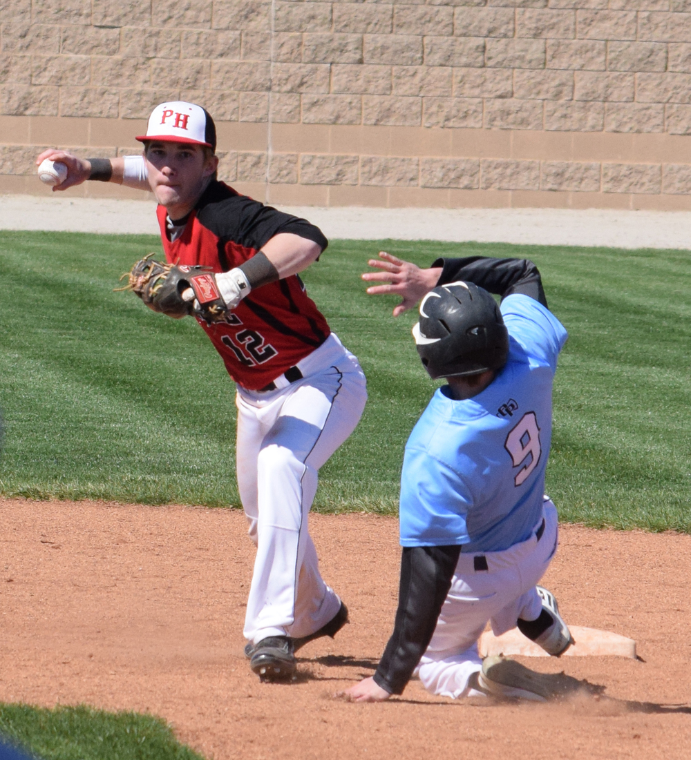 BRYCE MERENESS/Citizen photo Park Hill senior shortstop Chase McCollom attempts to turn a double play against Oak Park on Saturday, April 2 at Park Hill High School in Kansas City, Mo. Park Hill went on to split the scheduled doubleheader with a 9-8 win and a 3-0 loss.
