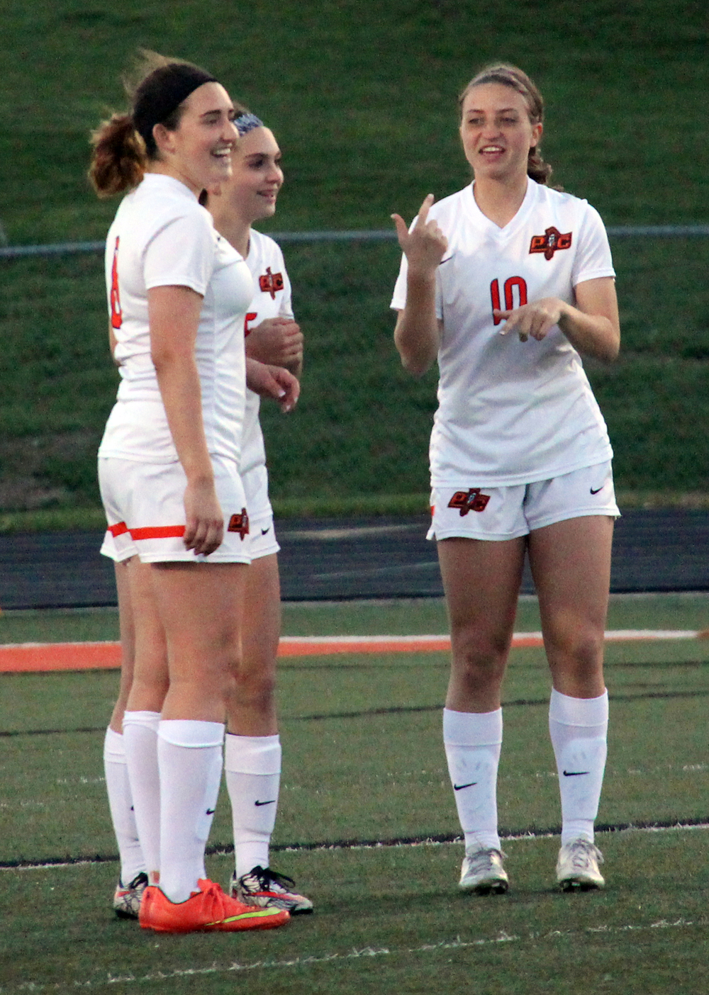 ROSS MARTIN/Citizen photo Platte County senior Haley Valentine, left, freshman Madeline Donnelli, center, and Boe share a laugh prior to the second half kickoff. The three start on the backline for Platte County.