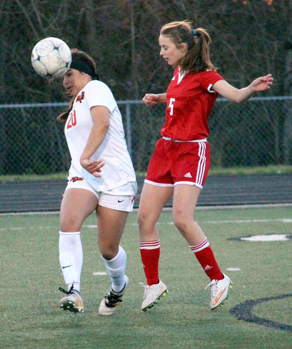 ROSS MARTIN/Citizen photo Platte County sophomore forward Destinee Smith heads the ball to herself against Raytown South defender Megan Percell. Smith scored a hat trick in the Pirates' 7-0 win against the Cardinals.