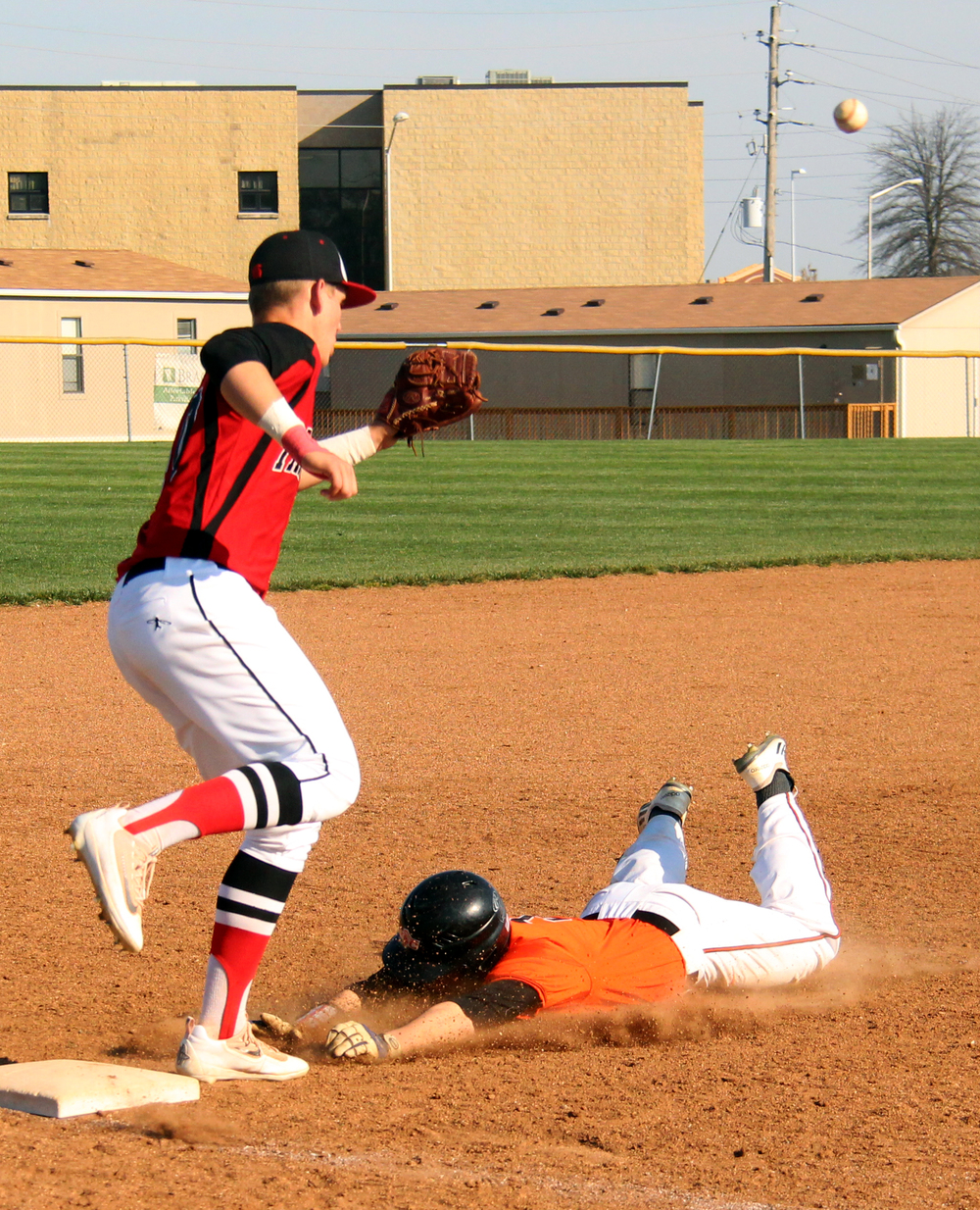 ROSS MARTIN/Citizen photo Platte County senior Colton Horn, right, slides into third base while Park Hill third baseman Preston Cross awaits a throw in the seventh inning of Platte County's win against Park Hill on Wednesday, April 13 at Platte County High School.