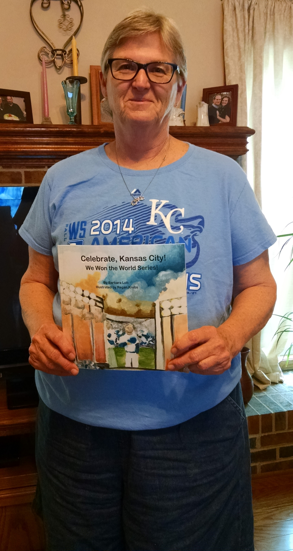 "JEANETTE BROWNING FAUBION/Citizen photo Barbara Lott of Weston, Mo. poses with a copy of her book, ""Celebrate, Kansas City! We Won the World Series!"" Lott self-published the book."