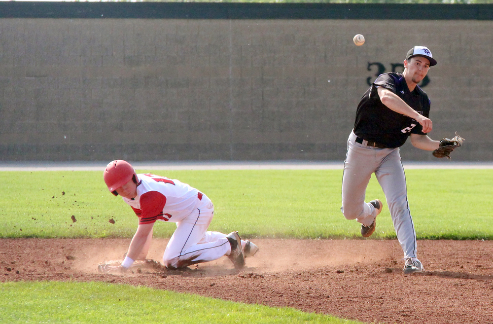 ROSS MARTIN/Citizen photo Park Hill South senior Ryan Hagen throws to first base trying to complete a double play after forcing out Park Hill runner Cody Youtsey, left.