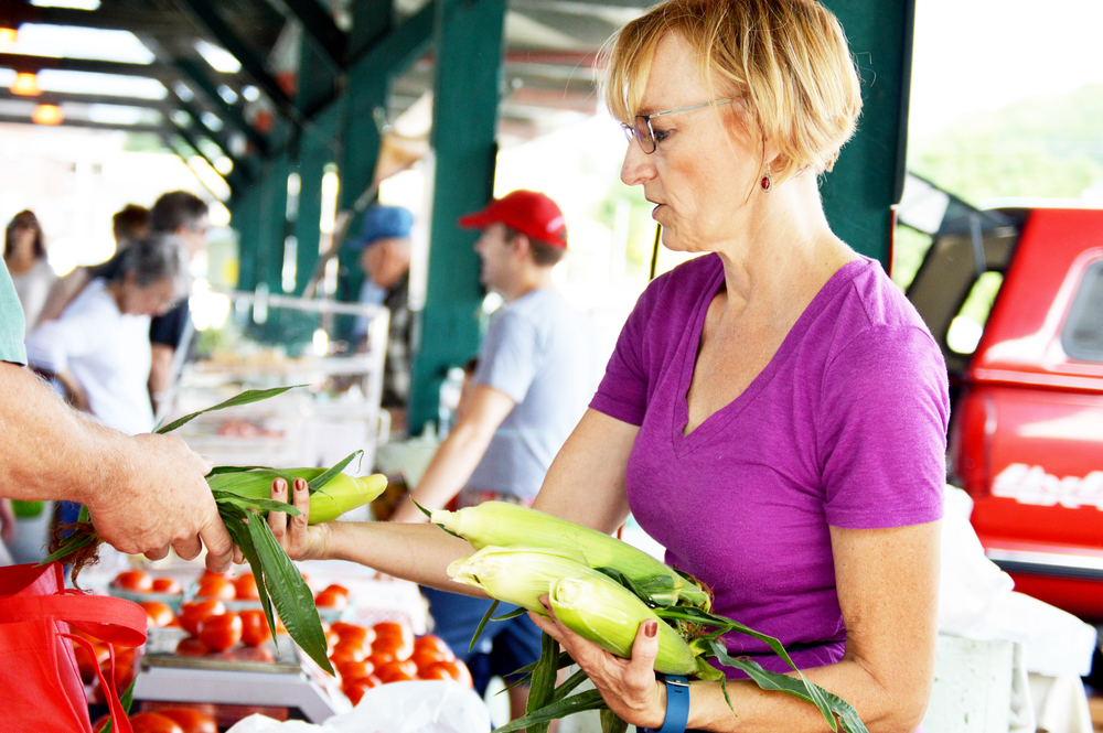 BRENT ROSENAUER/Citizen photo Shelly Oberdiek of Farley, Mo. sells some corn to a customer during the Parkville Farmer's Market on Saturday, July 9.