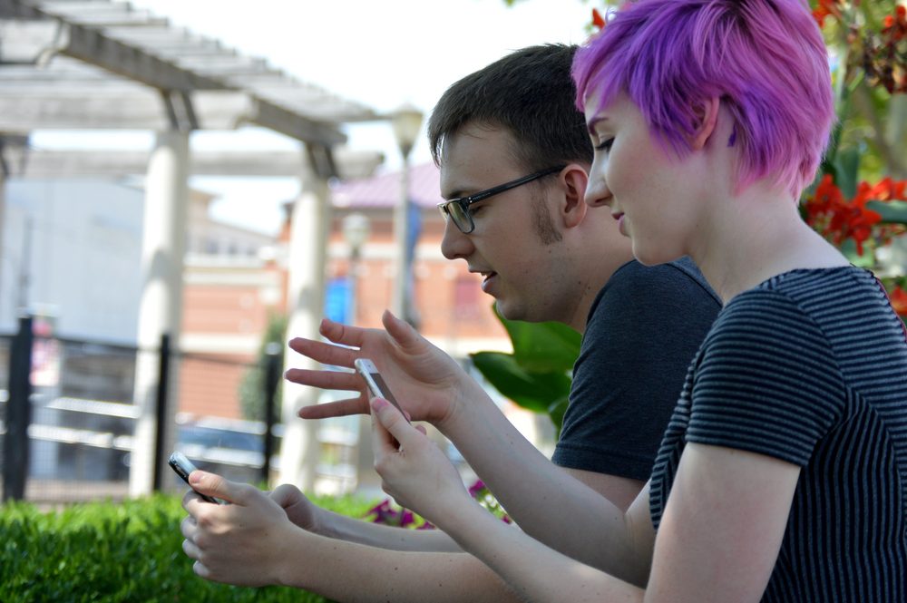 BRENT ROSENAUER/Citizen photo Perri Sturm (right) and Chase Bengston, both of Kansas City, Mo., play Pokemon Go on Monday, July 18 while sitting on a bench inside Zona Rosa in Kansas City, Mo. Platte County offers a myriad of good places for those playing the new mobile game.