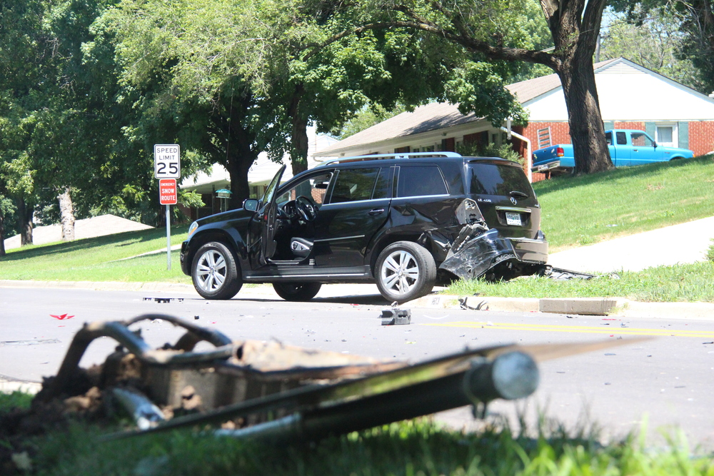 ROSS MARTIN/Citizen photo A Mercedes SUV sits in a yard on Fourth Street across the intersection with Blake Street after a two-vehicle accident Wednesday, July 20 in Platte City. A Platte County Sheriff's Office patrol vehicle (not pictured) also involved in the wreck appeared to have knocked down the street sign seen at front.