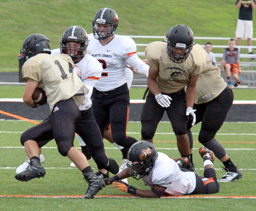 ROSS MARTIN/Citizen photo Platte County senior defensive back Cade Goettling finishes off a tackle on a play against Excelsior Springs during a preseason jamboree held Friday, Aug. 12 at Pirate Stadium. Pirates linebackers Austin Shoemaker (center) and Jason Young (bottom right) were also in on the play.