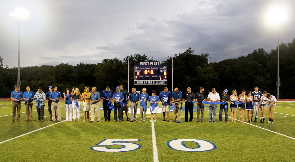 ROSS MARTIN/Citizen photo The West Platte School District held a ribbon-cutting ceremony for the new Rudolph Eskridge Stadium and Joe Collison Field on Friday, Aug. 19 before a scheduled football game between the Bluejays and Central Academy of Excellence. The 10-minute presentation came just ahead of inclement weather that forced the game's postponement. Those helping cut the ribbon, included, from left, Ben Vanderau (JE Dunn Construction), Scott Mead (JE Dunn), Muhannad Dinn (JE Dunn), high school principal Vince Matlick, assistant principal Ryan Ramey, district director of communications Stacy Shipman, Dr. Regina Knott, elementary school principal Rebecca Henshaw, Dr. Mark Harpst, Weston mayor Kent Stelljes, school board members Donald Wilson, Ryan Rotterman (vice president), Shane Bartee, Antonio Cutolo-Ring, Tracie Kalic, Ron Rowe (president), superintendent John Rinehart, Mark Franzen of HTK Architects, Gordon Kimble (HTK), director of maintenance Howard Hellebuyck, Dale Duncan (JE Dunn construction manager) and West Platte students Kaitlin Larison, Rachel Heili, Emily Norman, Jonah Vandel, Alexa Raney and Connor McNair.