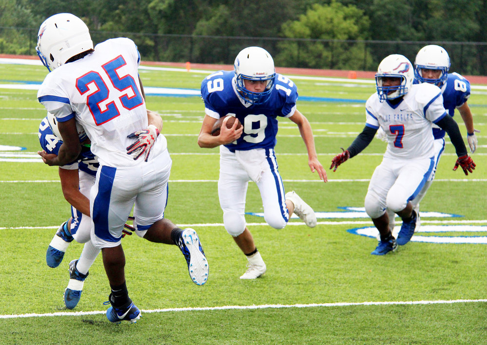 ROSS MARTIN/Citizen photo West Platte senior quarterback Nick Miller (19) weaves through the Central Academy of Excellence defense while running back Brayan Rodriguez, left, blocks during a game Saturday, Aug. 20 at the new Rudolph Eskridge Stadium in Weston, Mo.