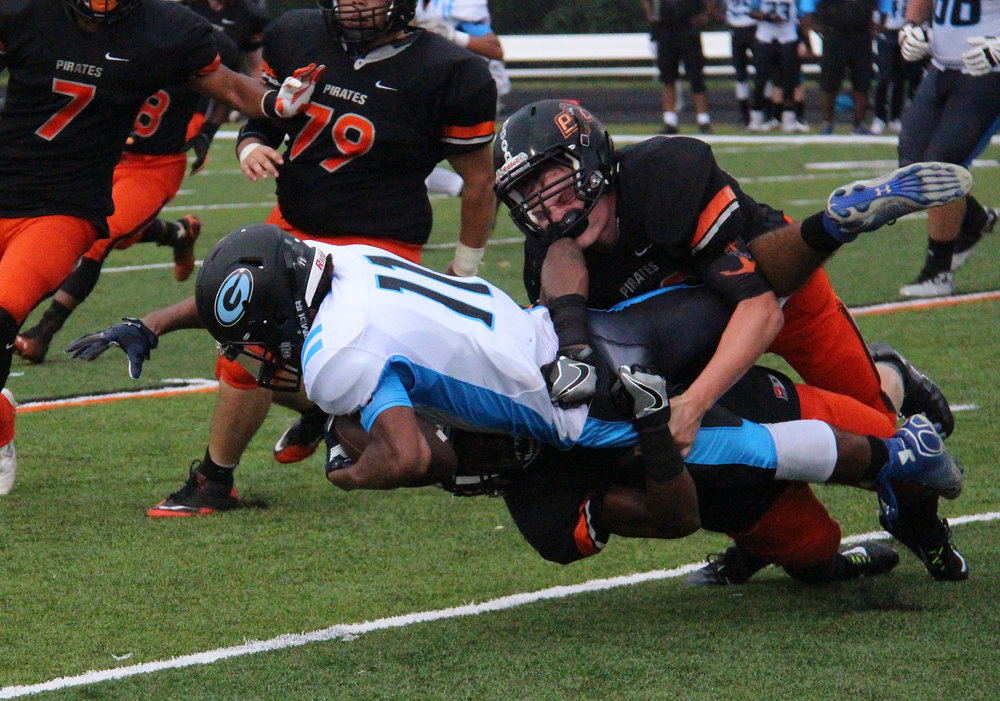 ROSS MARTIN/Citizen photo Platte County junior linebacker Dakota Schmidt, right, finishes off a tackle of Grandview running back Terrence Johnson with help from Pirates senior safety Kevin Neal, bottom, during their regular season opener Friday, Aug. 19 at Pirate Stadium. Platte County won 36-0.