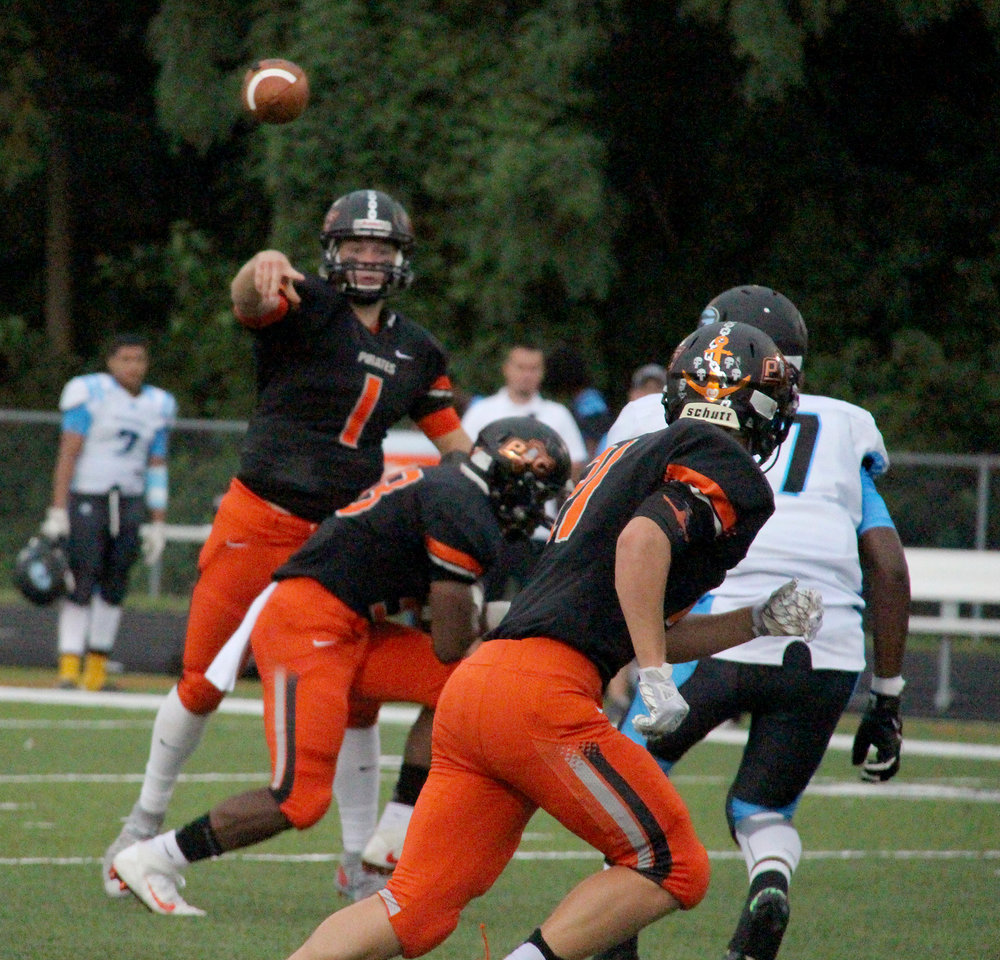 ROSS MARTIN/Citizen photo Platte County quarterback Justin Mitchell (1) throws a pass toward Hunter Tongate, front, during the first half against Grandview on Friday, Aug. 19 at Pirate Stadium.