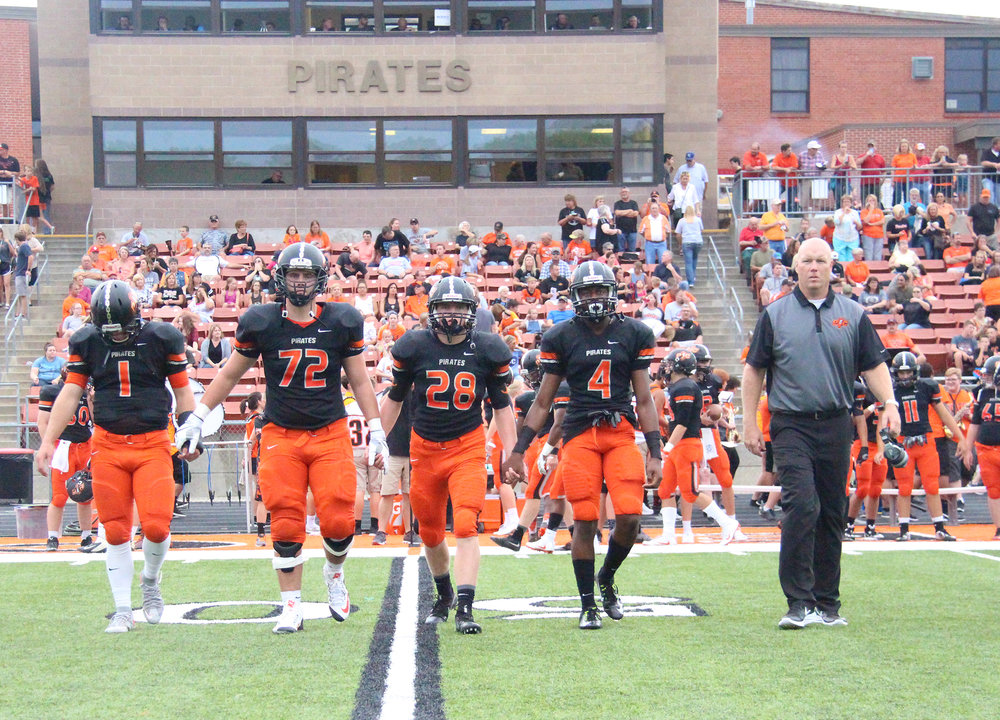 ROSS MARTIN/Citizen photo Platte County captains Justin Mitchell (1), Derek Kohler (72), Dakota Schmidt (28) and Kevin Neal (4) walk out with coach Bill Utz for the pregame coin toss Friday, Aug. 19 against Grandview at Pirate Stadium. The Pirates won the opener 36-0.