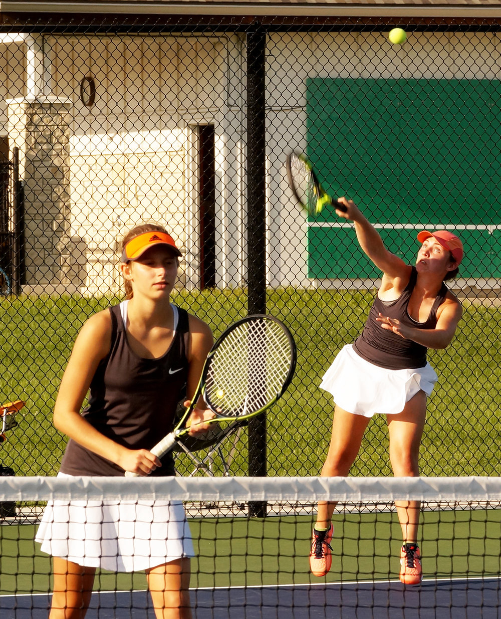 CHRIS PATTERSON/Citizen photo Platte County's Madalyn Ivy, right, hits a serve while doubles partner Hannah Valentine waits at the net against Liberty North on Monday, Aug. 29 in Liberty, Mo.