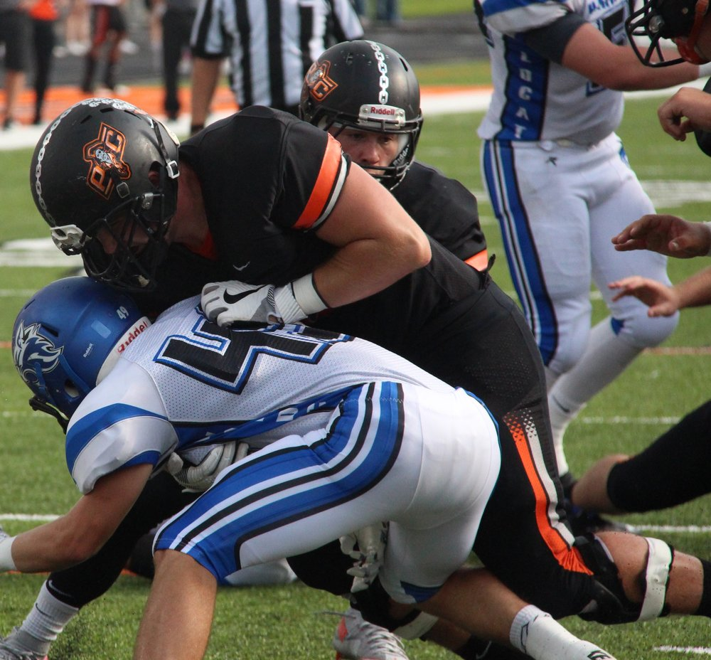 ROSS MARTIN/Citizen Editor Platte County senior left tackle Derek Kohler clears a path for Pirates senior quarterback Justin Mitchell, rear, on a 7-yard touchdown run Friday, Sept. 9 against Harrisonville at Pirate Stadium.