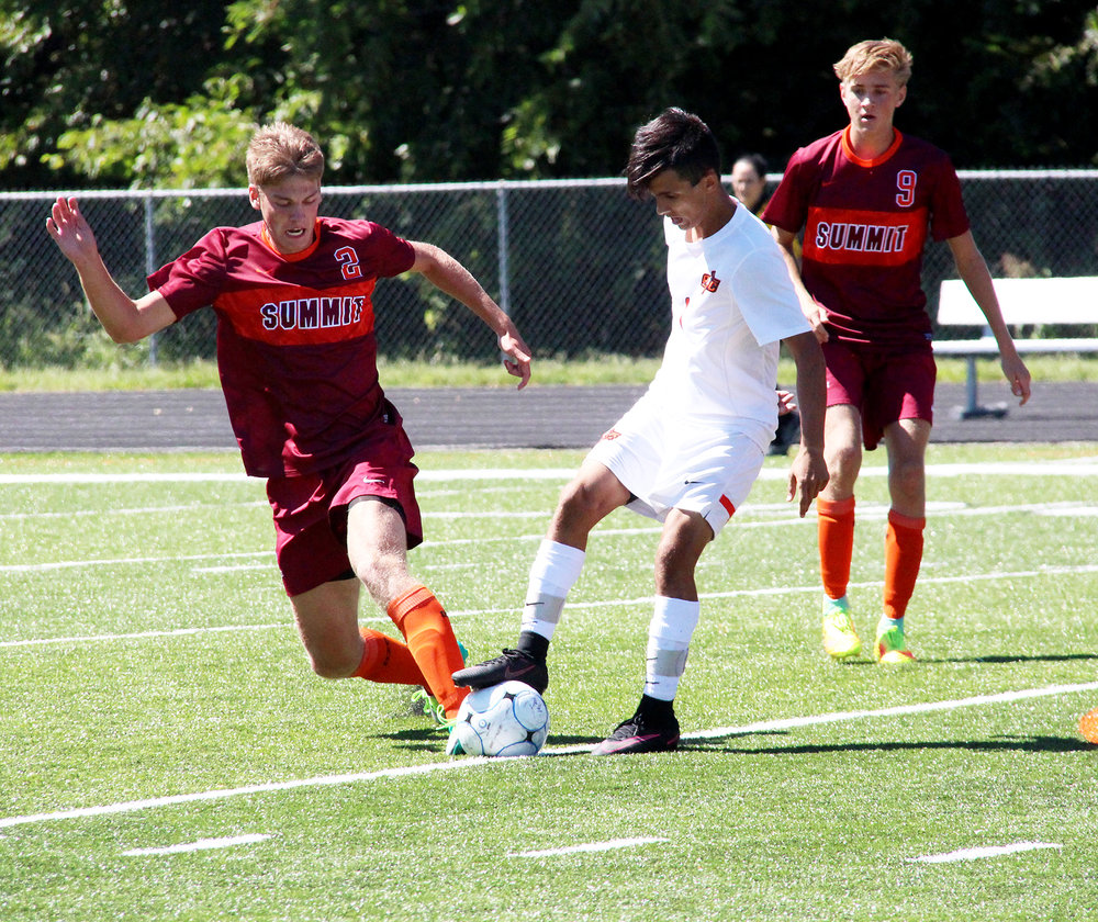 ROSS MARTIN/Citizen photo Platte County senior midfielder Chandler Peterson, center, works the ball between two Rockwood Summit defenders Saturday, Sept. 10 in a game at Pirate Stadium.
