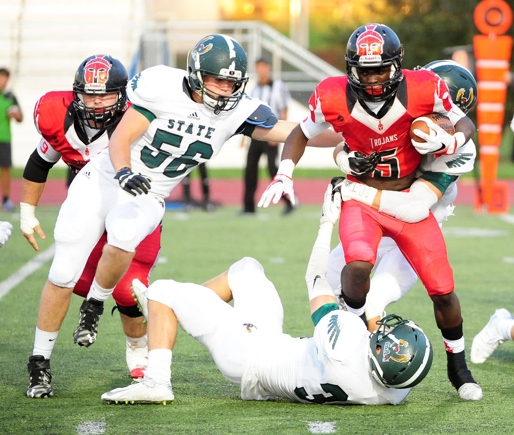 NICK INGRAM/Citizen photo Park Hill junior running back Dorian Clayton, right, tries to pull away from a pair of Lawrence Free State (Kan.) defenders during a matchup Friday, Sept. 16 at Park Hill District Stadium in Kansas City, Mo. Clayton played for the first time this season and ran for 222 yards.