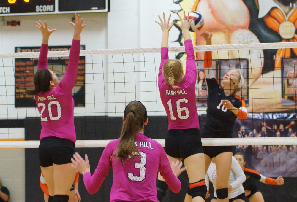 CHRIS PATTERSON/Citizen photo Platte County junior Kenzie Polley, right, hits into the Park Hill defense of Honor Foutch (16) and Rachel Pella (20) during a pool play match in the Platte County Invitational on Saturday, Sept. 17 at Platte County High School.