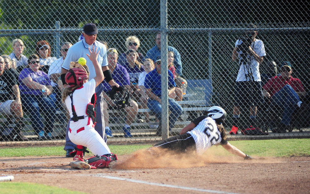 NICK INGRAM/Citizen photo Park Hill South senior Carolyn Stock (22) slides into home as Park Hill catcher Kali Day tries to field a throw during a game Monday, Oct. 3 at Park Hill South High School in Riverside, Mo.