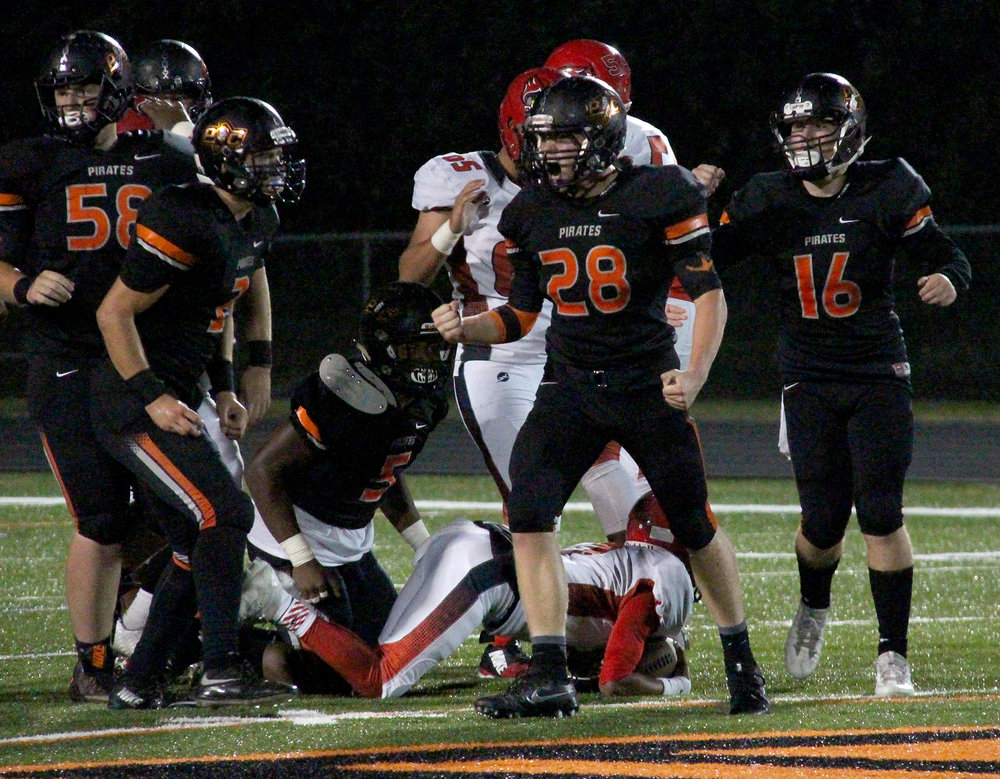 ROSS MARTIN/Citizen photo Platte County junior linebacker Dakota Schmidt (28) celebrates a stop with teammates including Gavin Hardman (16), Michael Smith (5), Austin Shoemaker (2) and Glen Gammill (58) during a 30-9 win against Raytown South on Friday, Sept. 30 at Pirate Stadium.