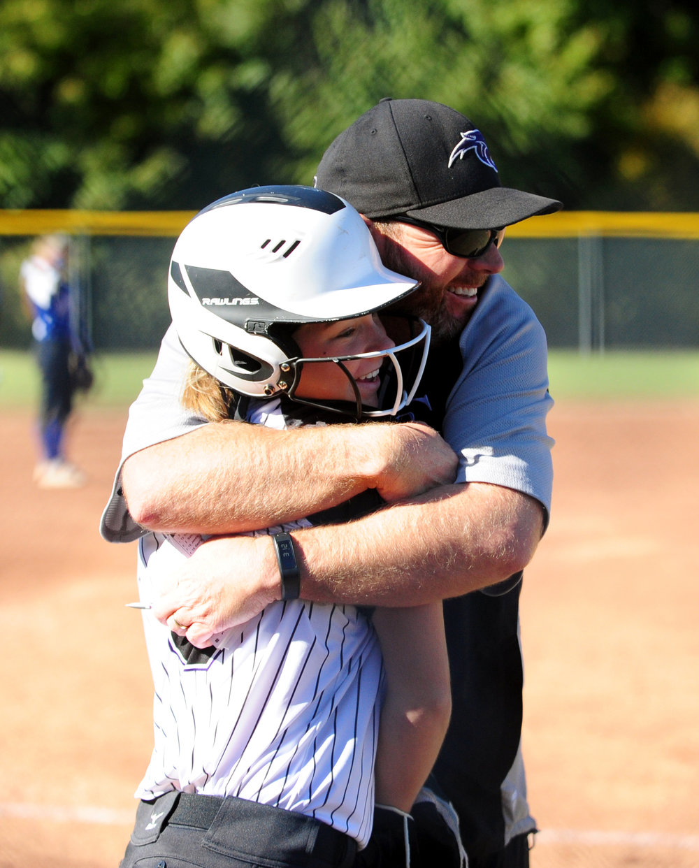NICK INGRAM/Citizen photo Park Hill South coach Josh Walker hugs sophomore second baseman Emma Beuerlein before she bats against Central.