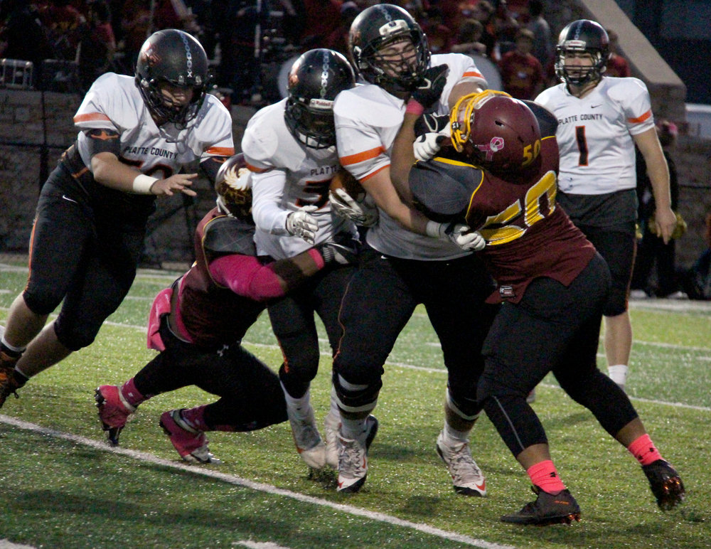 ROSS MARTIN/Citizen photo Platte County running back Mike McNair, center, tries to squeeze through a hole while senior linemen Derek Kohler, right, and Austin Gammill, left, block against Winnetonka on Friday, Oct. 7 at North Kansas City District Stadium in North Kansas City, Mo.