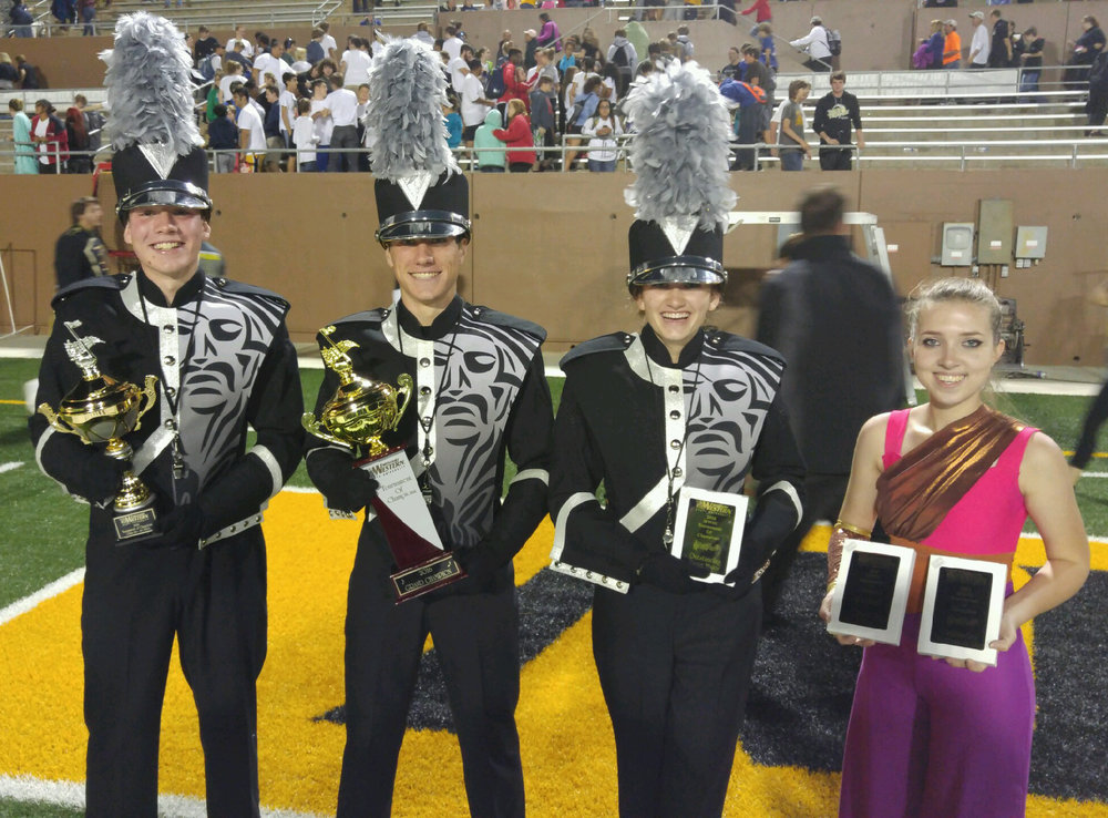 Contributed photo Platte County High School Pirate Pride Marching Band drum majors (from left) John Morrione, Spencer Kunz and Audrey Puntney. and color guard captain Kalista Hill show off the awards won during the Missouri Western State University Tournament of Champions competition Tuesday, Oct. 11 in St. Joseph, Mo. Platte County took the title of grand champion for the second year in a row.