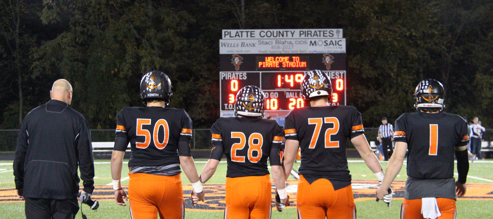 ROSS MARTIN/Citizen photo Platte County football coach Bill Utz, left, and captains (from left) Austin Gammill, Dakota Schmidt, Derek Kohler and Justin Mitchell walk onto the field prior to a game with Winnetonka on Friday, Oct. 21 at Pirate Stadium.