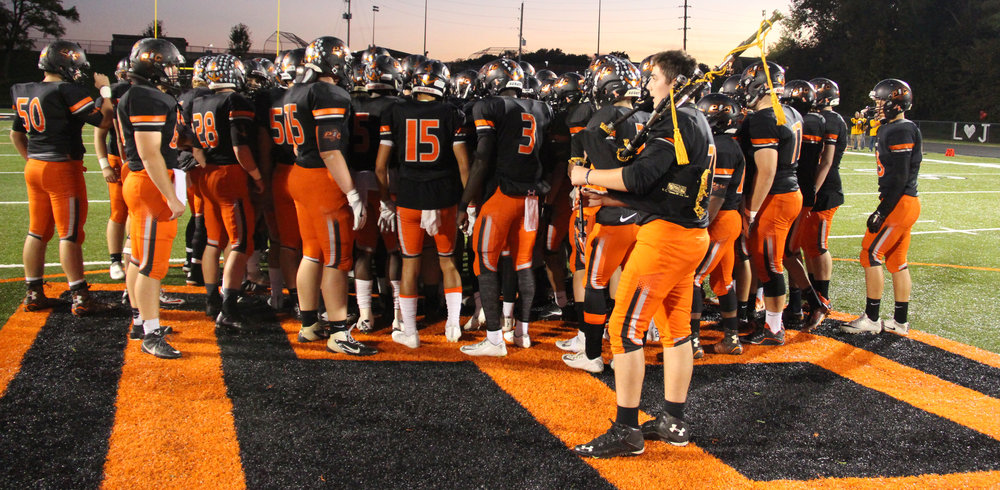 ROSS MARTIN/Citizen photo Platte County offensive lineman Ryan Lett (front right) played the bagpipes during the football team's entrance to the field Friday, Oct. 21 at Pirate Stadium. The players were huddling around the football in memory of Landon Jaros prior to the game.