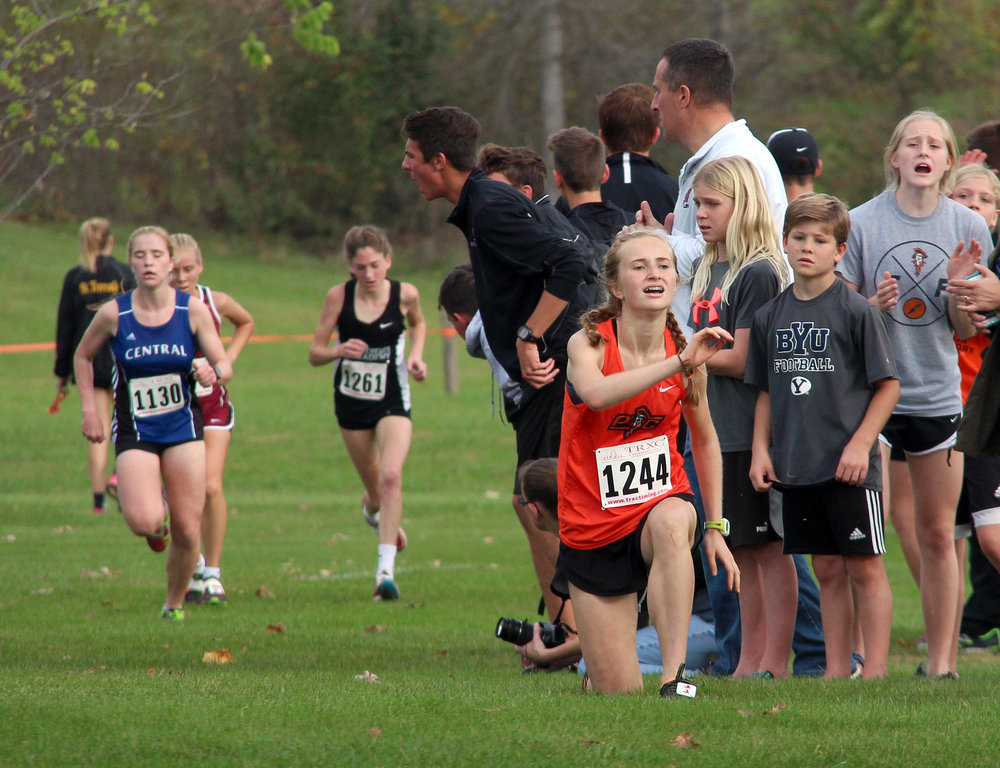 ROSS MARTIN/Citizen photo Platte County sophomore Jessica Clark tries to get back to her feet after falling near the finish line of the Class 4 Sectional 4 race Saturday, Oct. 29 at Jesse James Park in Kearney, Mo. She managed to finish the race in 29th, qualifying for the Missouri State Track and Field Championships.