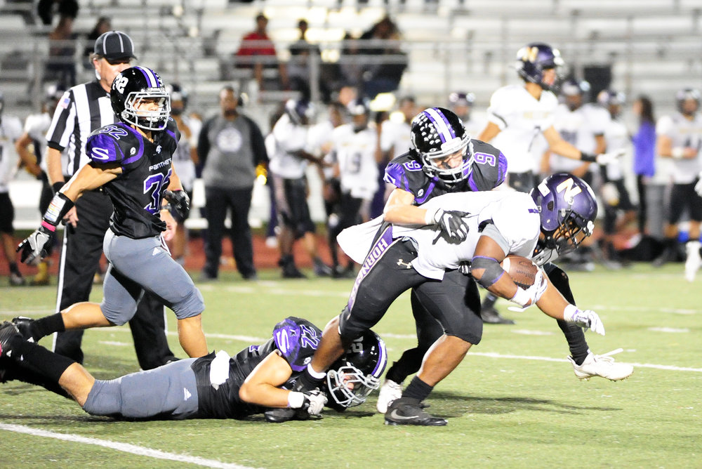 NICK INGRAM/Citizen photo Park Hill South senior Everett Horton (22) and sophomore Payton Murray (9) tackle North Kansas City senior DJ Whitmill on Friday, Oct. 29 at Park Hill District Stadium in Kansas City, Mo.