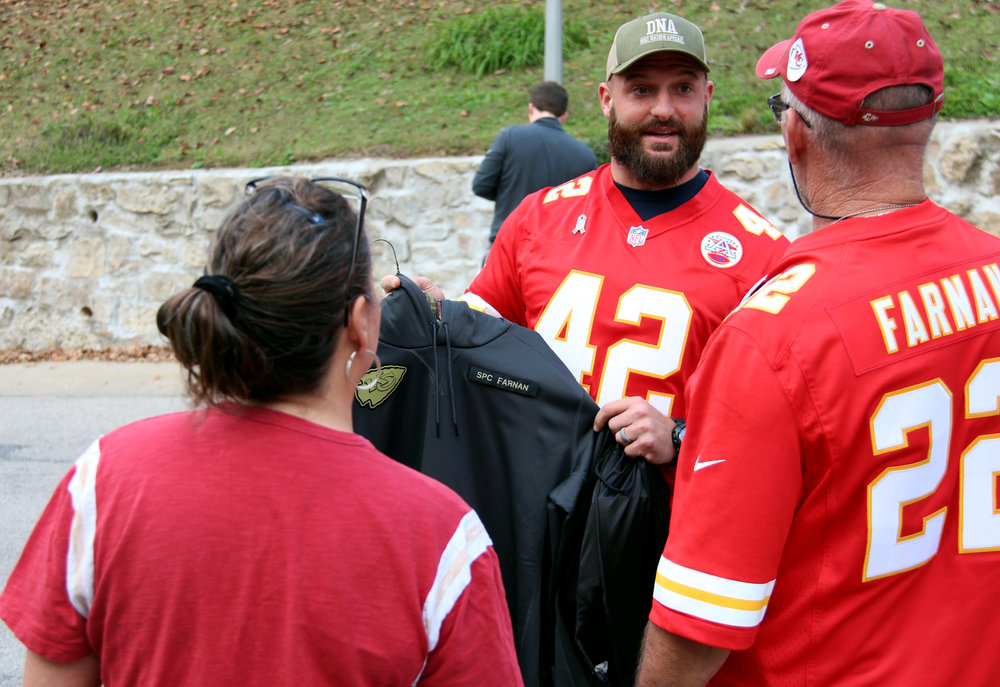 ROSS MARTIN/Citizen photo Kansas City Chiefs fullback Anthony Sherman presents Patrick and Deann Farnan with a custom hooded sweatshirt honoring their son Colby Farnan, killed at the age of 22 while serving the U.S. Army in Iraq. Sherman wore the shirt prior to the Chiefs' Sunday, Nov. 6 game against the Jacksonville Jaguars, and he made the presentation Monday, Nov. 7 at the Farnans' home in Weston, Mo.