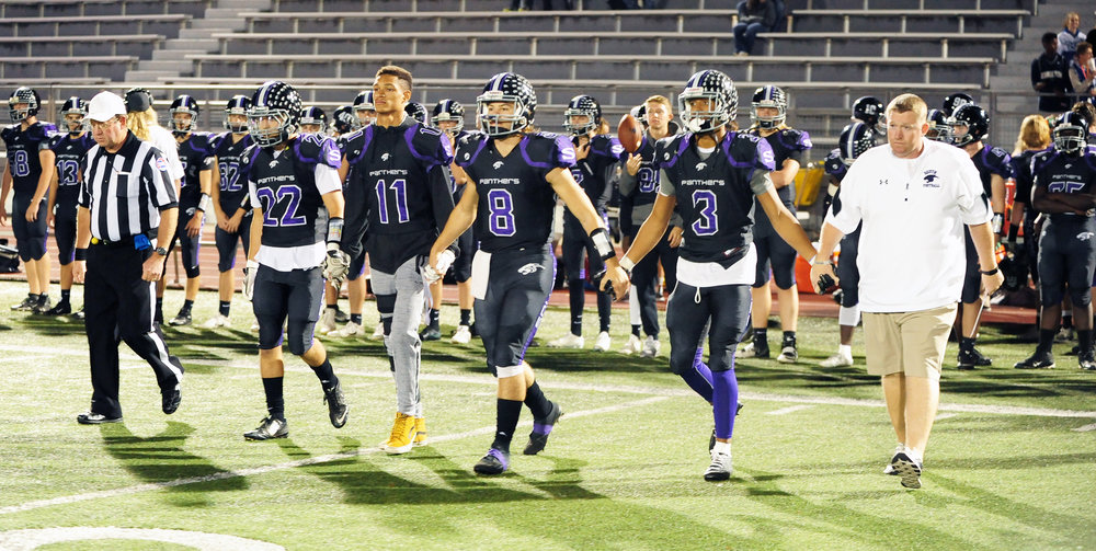 NICK INGRAM/Citizen photo Park Hill South captains Everett Horton (22), Dillon Thomas (11), Zach Suchanick (8) and Jake Springer (3) walk out for the coin toss with coach Mike Sharp, right, prior to the Class 5 District 7 championship game against Fort Osage on Friday, Nov. 4 at Park Hill District Stadium in Kansas City, Mo.