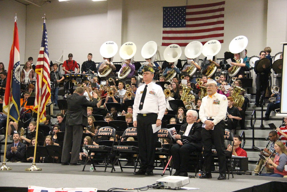 ROSS MARTIN/Citizen photo Platte County High School director of bands Dr. Jay Jones, left, conducts the Traditions Band while VFW Post 455 members Robert Munsey (front left) and Martin LeGault (front right) stand next to VFW Post 455 Auxiliary member Marcella Cannon (seated) during a Veterans Day assembly on Friday, Nov. 11 at Platte County High School.