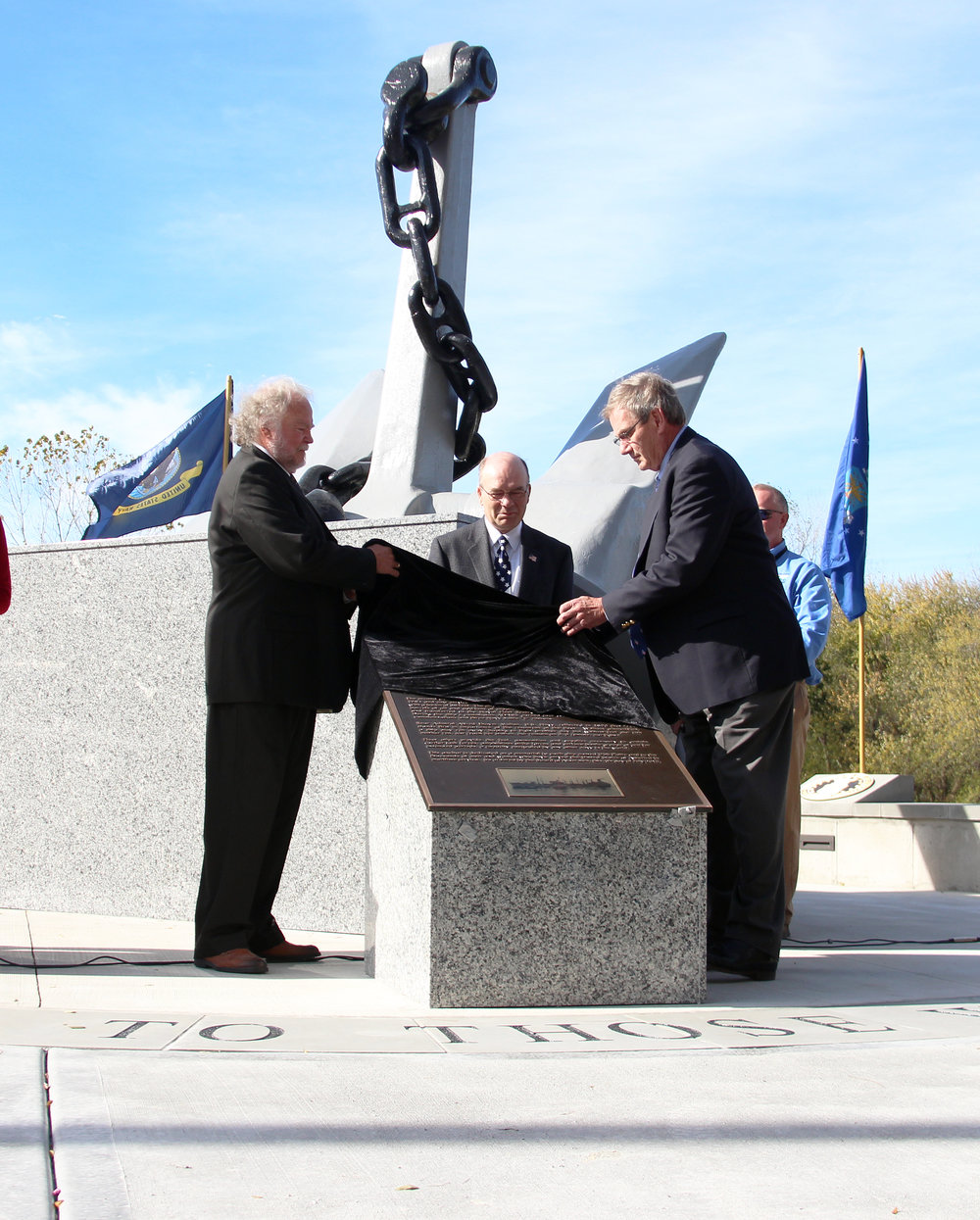 ROSS MARTIN/Citizen photo From left, Rev. Michael Lazio of Bethel House of Prayer, Platte City mayor Frank Offutt and Platte County Circuit Court judge James Van Amburg unveil a plaque at the new Platte City Veterans Monument during a ceremony on Veterans Day, Friday, Nov. 11 at Settler's Crossing Park in Platte City.