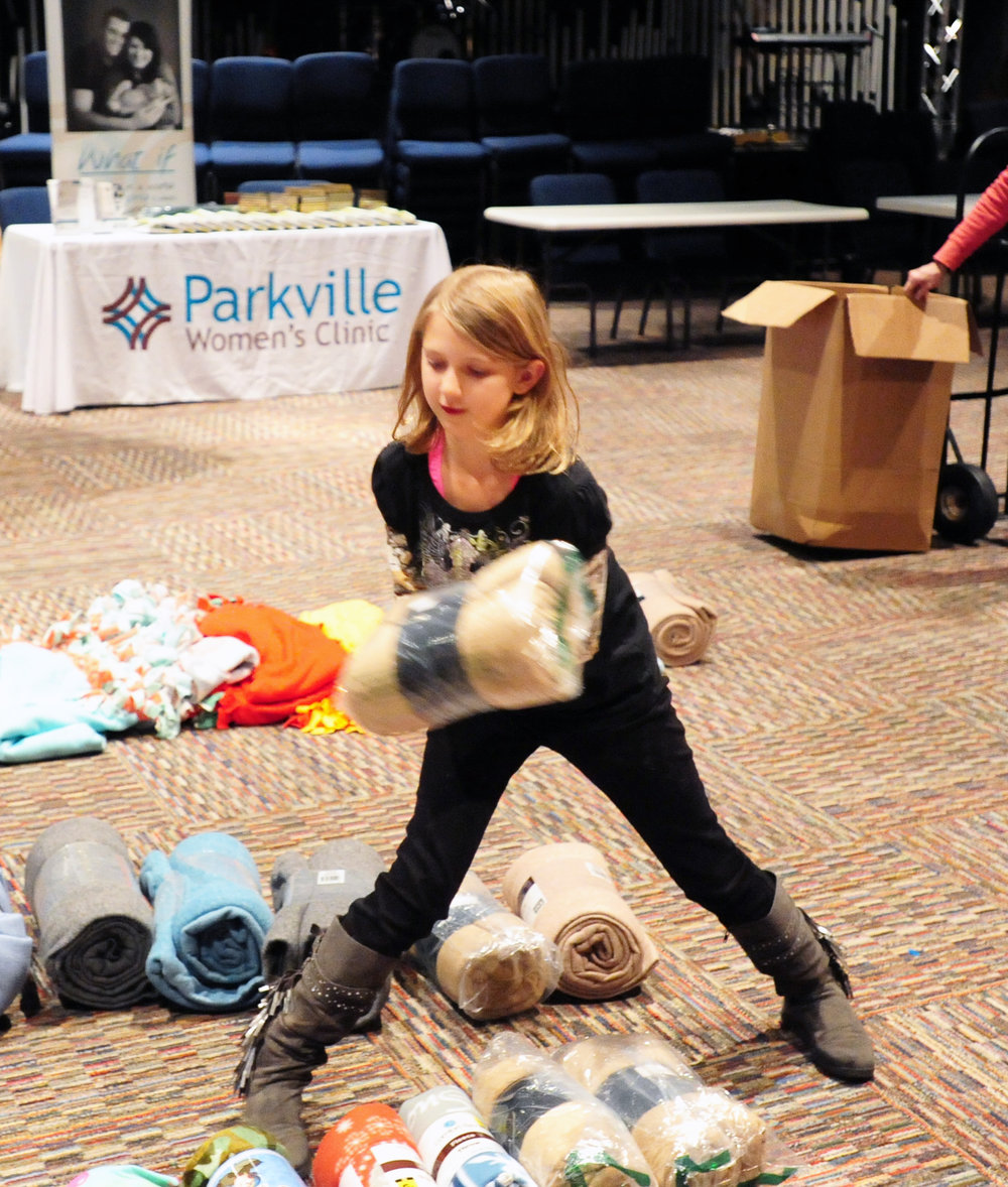 NICK INGRAM/Citizen photo Victoria Robinson, 9, sorts out the blankets she collected for the annual Day of Hope event held Saturday, Dec. 3 at the Rock of KC Church in Kansas, City, Mo.