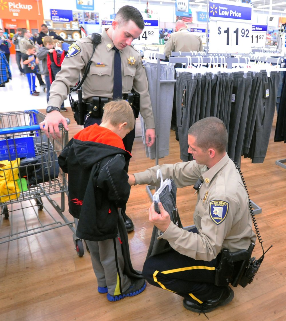 NICK INGRAM/Citizen photo Platte County Sheriff's Office deputies Andy Servaes, right, and Richard Wood help pick out clothes during the annual Shop with a Cop event on Saturday, Dec. 3 at a Wal-Mart Supercenter in Kansas City, Mo.