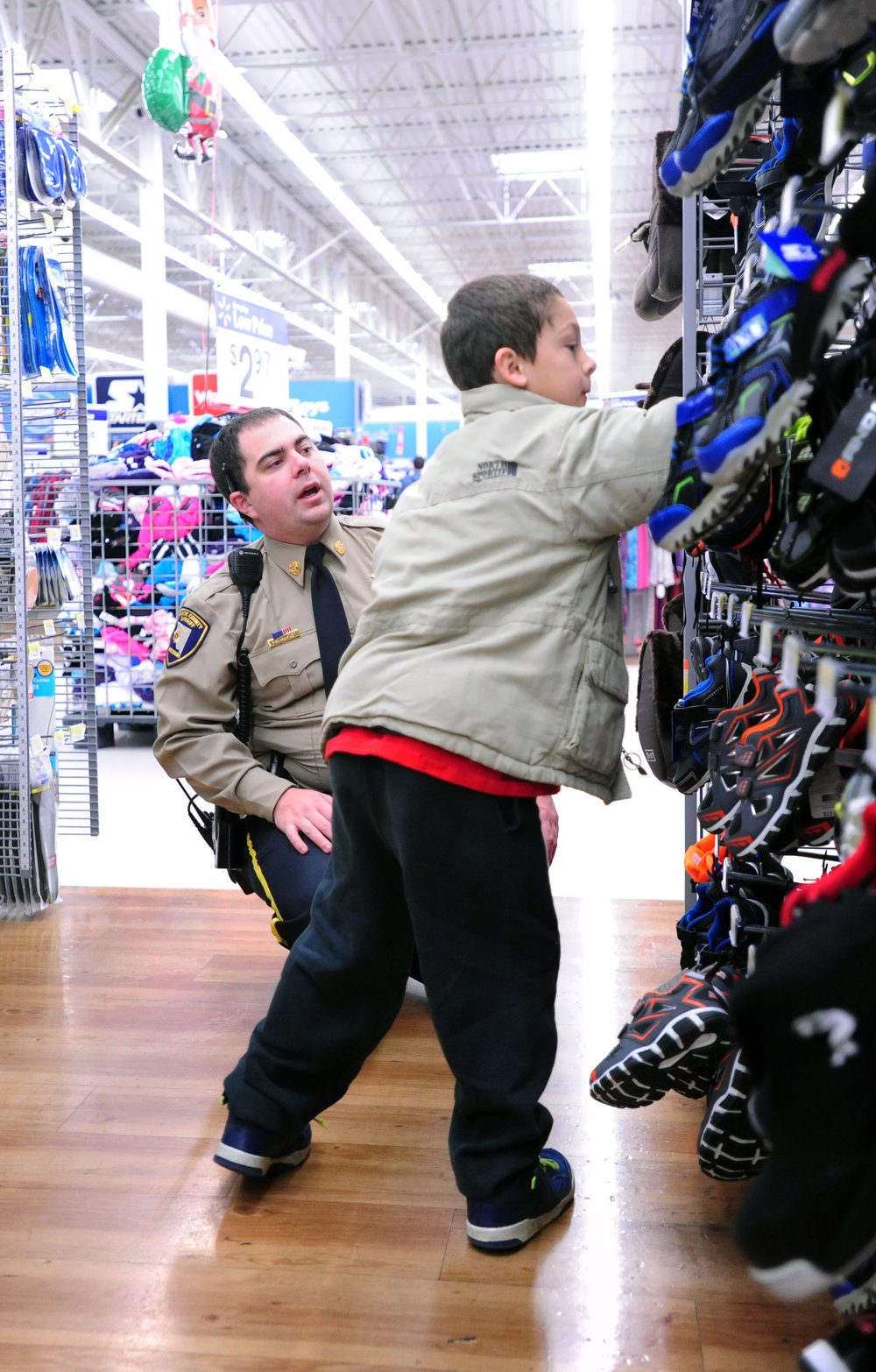 NICK INGRAM/Citizen photo Platte County Sheriff's Office deputy Richard Mayse, left, helps pick out shoes with Jackson Schafer, 7, at a Wal-Mart Supercenter on Saturday, Dec. 3 in Kansas City, Mo.