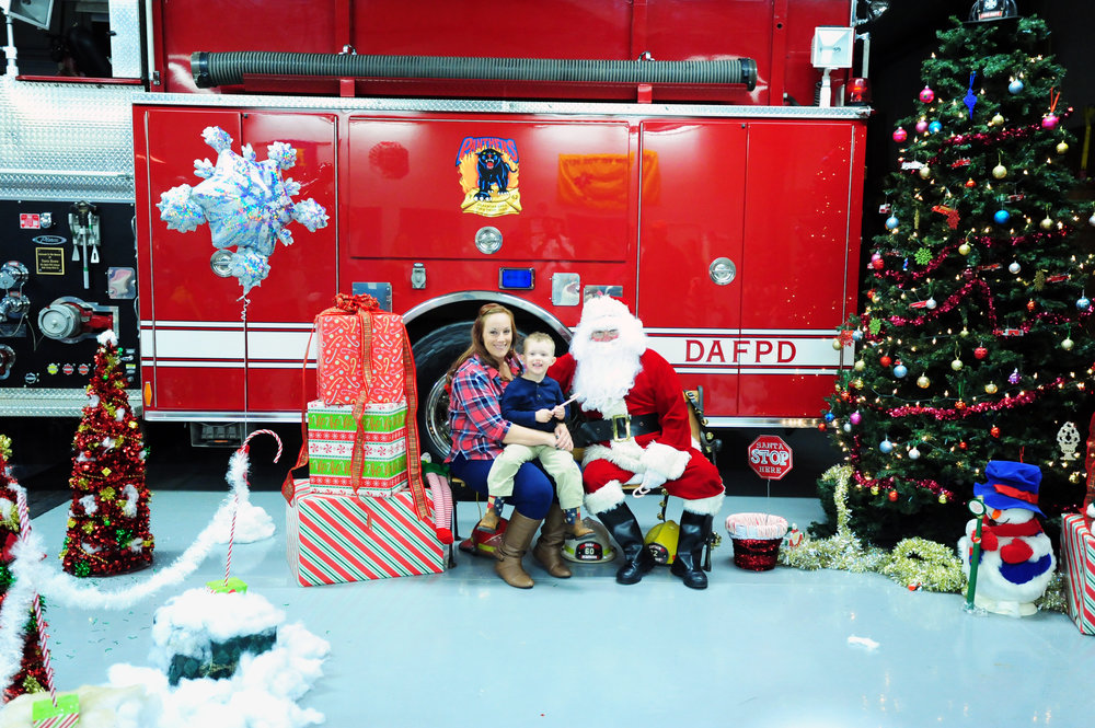 NICK INGRAM/Citizen photo Sarah Swanstone and Calvin Swanstone, 3, from Dearborn, Mo. sit with Santa Claus during Cookies with Santa at the Dearborn Area Fire Protection District station on Saturday, Dec. 3 in Dearborn, Mo.