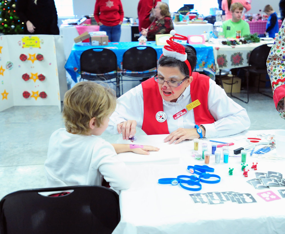 NICK INGRAM/Citizen photo Cindy Johnson of Platte City applies glitter to a child's hand during Chirstmas in Dearborn on Saturday, Dec. 3 in Dearborn, Mo.