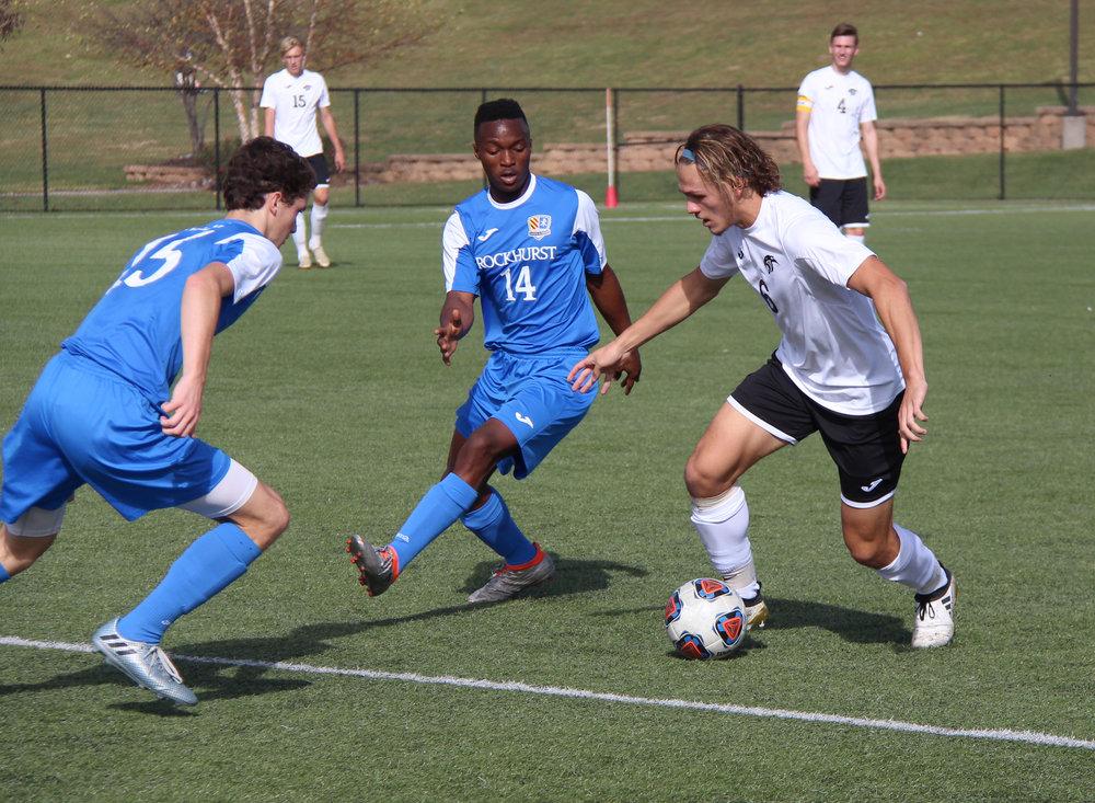 ROSS MARTIN/Citizen photo Park Hill South senior Ryan DiBernardo looks to dribble past a pair of Rockhurst defenders.
