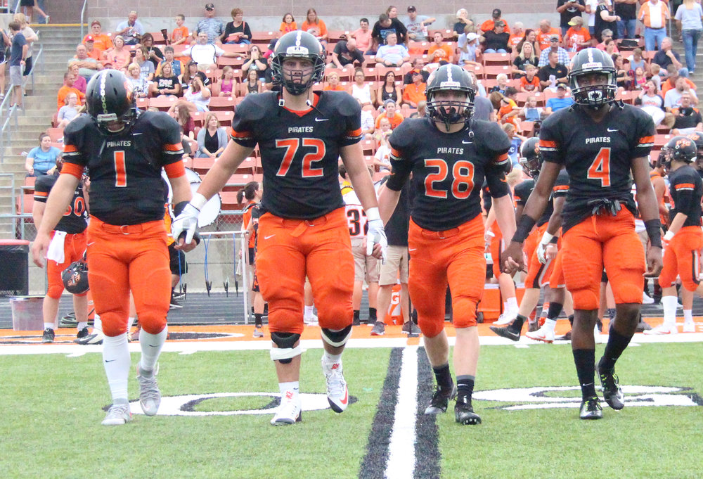 ROSS MARTIN/Citizen photo Platte County quarterback Justin Mitchell (1), offensive tackle Derek Kohler (72), linebacker Dakota Schmidt (28) and defensive back Kevin Neal (4) take the field as captains ahead of the Pirates' season-opener this past August against Grandview at Pirate Stadium. All four were all-state players this year.
