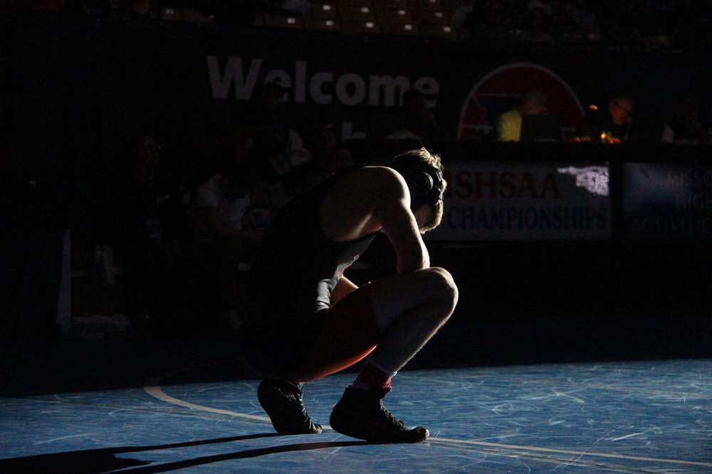ROSS MARTIN/Citizen photo Platte County senior Ethan Karsten kneels at the edge of the mat Saturday, Feb. 20 prior to the Class 3 Missouri State Wrestling Championships' Class 3 145-pound title bout at Mizzou Arena in Columbia, Mo. He won his third state title just days after learning of his older brother's death.